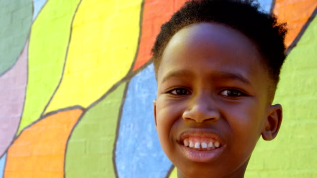 front view of happy african american schoolboy standing against wall in school 4k - невинность стоковые видео и кадры b-roll