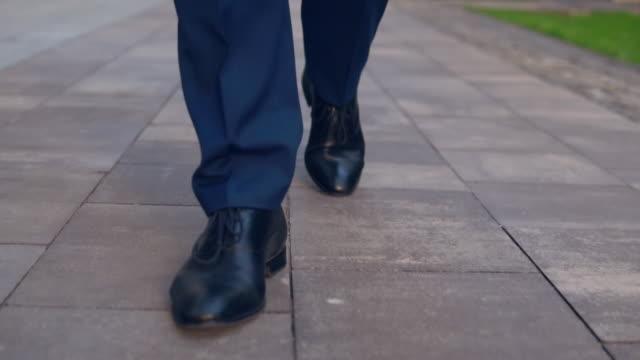 vidéos et rushes de vue de face des pieds mâles au transport sur le trottoir - costume habillé
