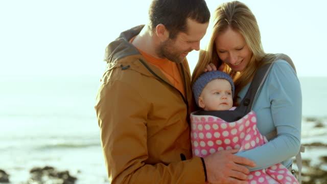 4 k 晴れたビーチで赤ちゃんを見て半ばアダルト白人親の正面図 - 息子点の映像素材/bロール