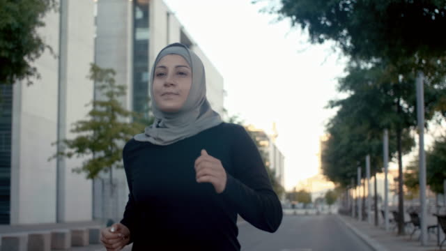 front view of muslim woman in hijab running in berlin (slow motion) - abbigliamento religioso video stock e b–roll