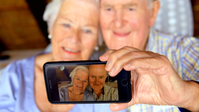 Front view of old Caucasian senior couple taking selfie with mobile phone at comfortable home 4k Front view of old Caucasian senior couple taking selfie with mobile phone at comfortable home. They are smiling and relaxing at home 4k telephone receiver stock videos & royalty-free footage