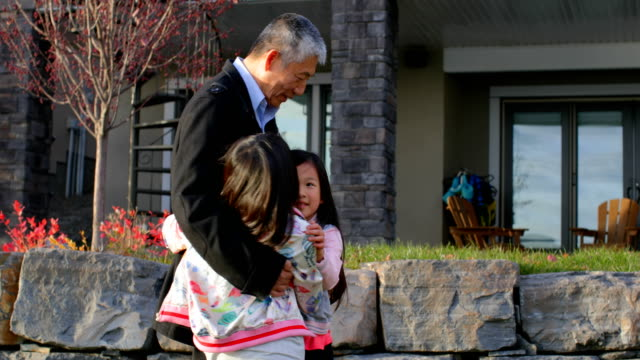 Front view of old senior asian grandfather embracing her granddaughters in outside the home 4k video
