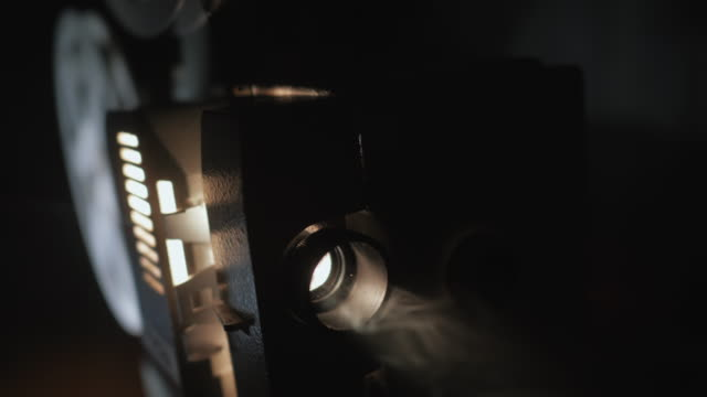 Front view of old-fashioned antique Super 8mm film projector,projecting beam of light in dark room next to stack of unraveled film reels.vintage theater spot light on black curtain with dust floating video