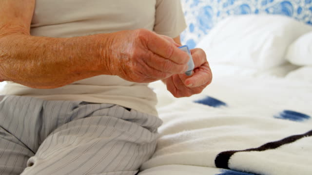 Front view of senior Caucasian man checking blood sugar level on bed in a comfortable home 4k video