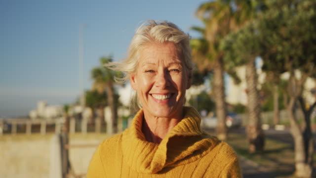vídeos y material grabado en eventos de stock de vista frontal de la mujer mayor junto a la playa - embarcadero