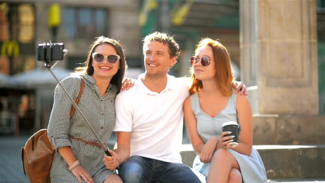 Front View of Three Happy Friends Taking Selfie Using Smartphone Outdoors on the City Square During Sunny Summer Day. Two Amazing Girls and One Boy Smiling Looking at the Camera video