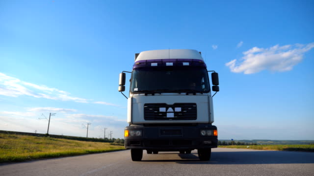 Front view of truck driving on a highway. Lorry rides through the countryside with beautiful landscape at background. Slow motion Close up Front view of truck driving on a highway. Lorry rides through the countryside with beautiful landscape at background. Slow motion Close up front view stock videos & royalty-free footage