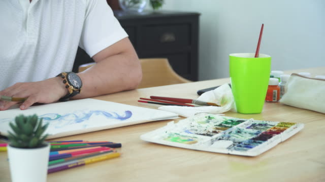 front view of watercolor paint and equipment such as paintbrush and part Asian handsome man painting one paper page with watercolor to create artist skill and imagination. Concept of young adult and leisure activity at the weekend.