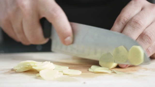 Front view of young man chef cut thin slices of a piece of ginger with knife on cutting Board. video