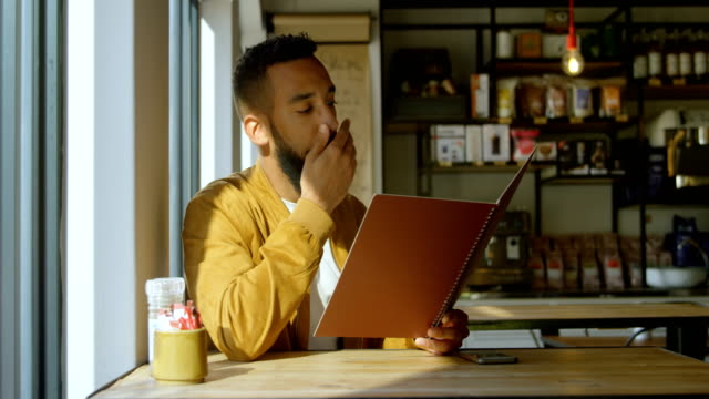 Front view of young mixed-race man looking at menu in cafe 4k Front view of young mixed-race man looking at menu in cafe. Thoughtful young mixed-race man sitting in cafe 4k menu stock videos & royalty-free footage