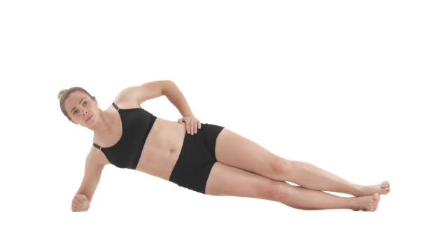front view portrait of young sportswoman in side plank position for strong core, back and abdominal muscles. Isolated on white background.