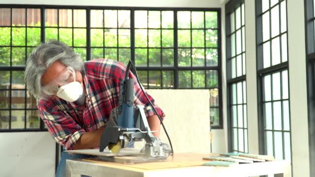vídeos de stock e filmes b-roll de front view: senior man tilter cutting tile with electric tile cutter - obras em casa janelas