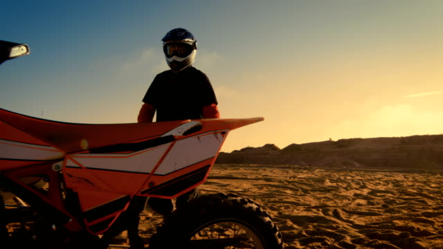 Front View Shot of the Professional Motocross Driver Saddles His FMX Dirt Bike on the Sand/ Dirt Track. video