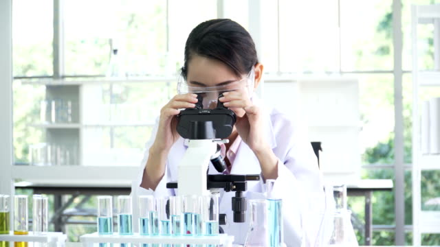 front view: smiling of Mid female Japanese scientist while doing her research on optical microscope
