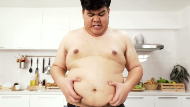 front view: thai overweight man feel anxiety on a big belly - furioso video stock e b–roll