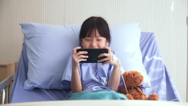 vordere ansicht: thai mädchen haben smartphone, einsamkeit auf der krankenstation zu ignorieren - geduld stock-videos und b-roll-filmmaterial