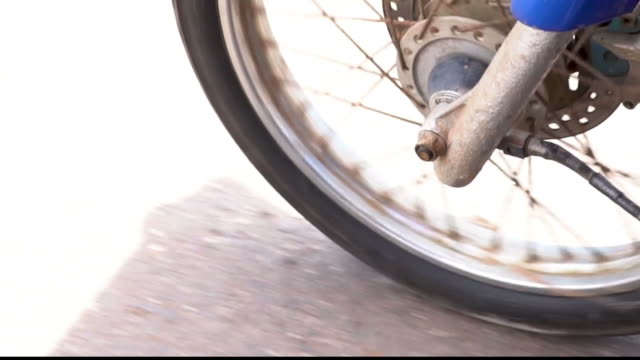 Front wheel of Motorbike spinning and moving forward on the road. Automobile engine running closeup