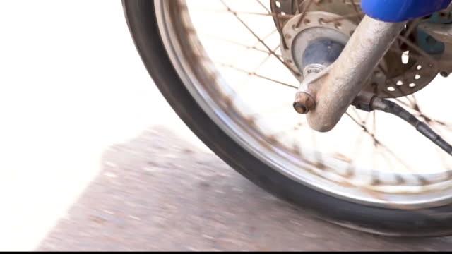 framhjulet av motorcykel spinning och framåt på vägen. bilmotor kör närbild - wheel black background bildbanksvideor och videomaterial från bakom kulisserna