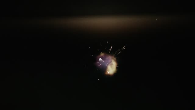Frontal muzzle flash from shot in black gun chamber. Flashing gunfire slow-motion.