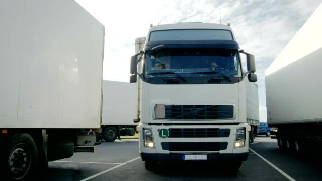 framifrån av vit semi truck med cargo trailer driver in parkering och parker med andra fordon. - stationär bildbanksvideor och videomaterial från bakom kulisserna