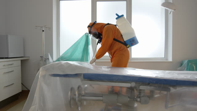 Frontline Coronavirus Worker in Hazmat Suit Disinfecting Operating Theater from COVID-19