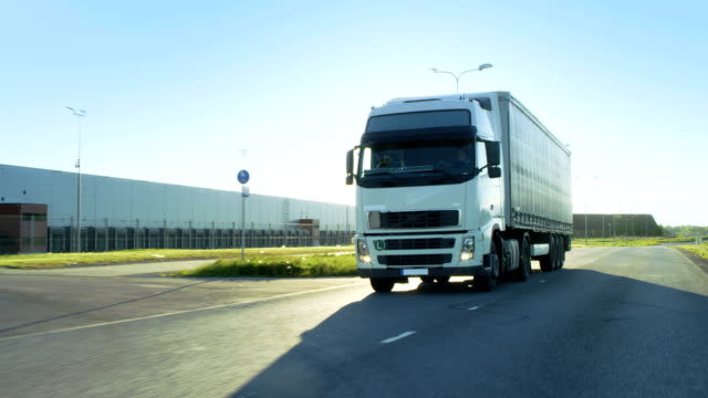 front-view camera follows semi truck with cargo trailer driving on a highway. he's speeding through industrial warehouse area while sun shines and no other vehicles are on the road. - icona supermercato video stock e b–roll