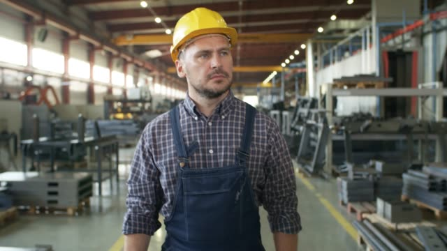 Frowning engineer walking along factory floor - vídeo