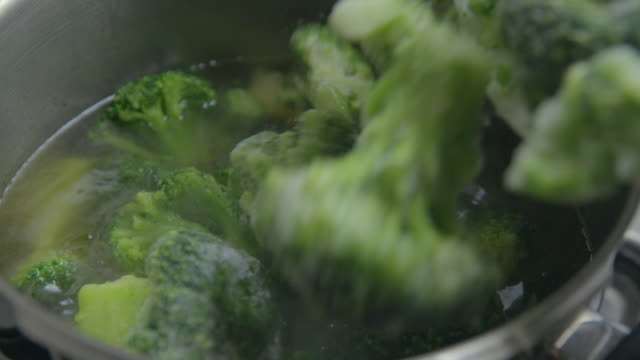 frozen broccoli cooking slow motion - broccolo video stock e b–roll
