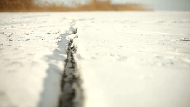 crepa della superficie del lago ghiacciata nella giornata di sole - ghiaccio galleggiante video stock e b–roll