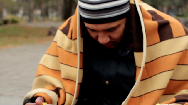 Frozen man covered with blanket asking for alms in the street, homelessness video