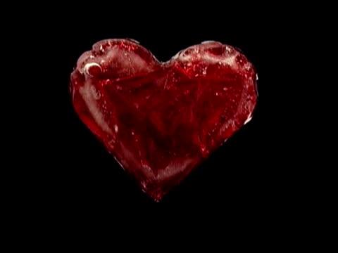 frozen red heart defrosts as starts beating isolated on black - donmuş su stok videoları ve detay görüntü çekimi