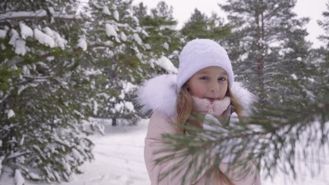 Frozen teenager girl while snowfall in winter forest while walking in frosty day