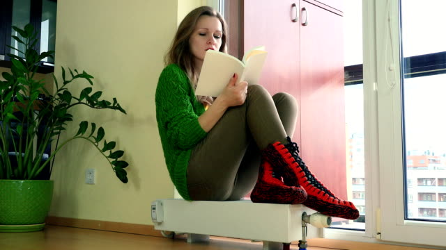 Frozen Woman Reading Book Sitting On Radiator And Adjusting Thermostat. video