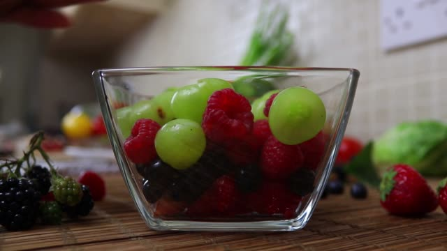 vídeos de stock e filmes b-roll de fruit bowl preparation - part 5 - adding blackberry in bowl - saladeira