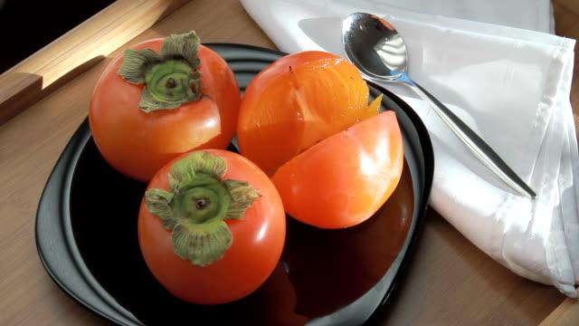 vídeos de stock e filmes b-roll de sobremesa de fruta num tabuleiro da luz solar - diospiro