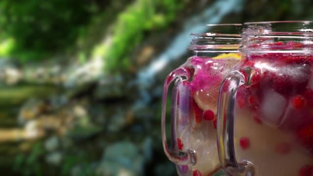 fruktdrycker på vattenfall bakgrund - konserveringsburk bildbanksvideor och videomaterial från bakom kulisserna