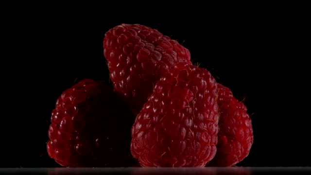 Fruit of raspberry color burgundy are rotating on black background. Close up video