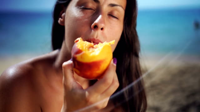 Fruit refreshment in hot summer day Young woman eating and enjoying peach on a sandy beach. Montage. peach stock videos & royalty-free footage