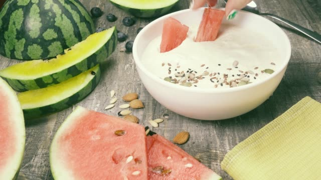 Fruit smoothiebowl on the table near the fruit Women's hand decorated with slices of yellow and red watermelon yogurt smoothies with sesame seeds in a white bowl sesame stock videos & royalty-free footage