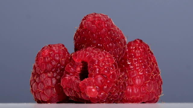 Fruits of ripe raspberry swirl on a light gray background. Close up video