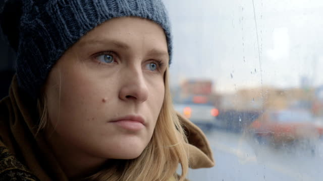 Frustrated and sad woman traveling by bus on rainy day video