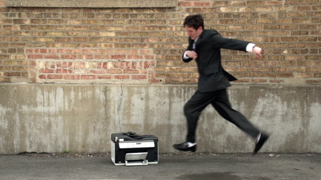 Frustrated business man kicking a printer video