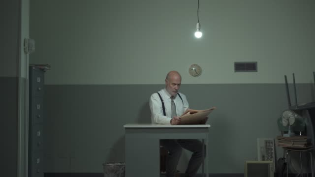 Frustrated businessman reading a newspaper in his office