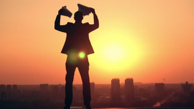 frustrated corporate employee urban city view silhouette businessman with documents in the early morning outdoors slow motion sunrise sky horizon over land stock videos & royalty-free footage