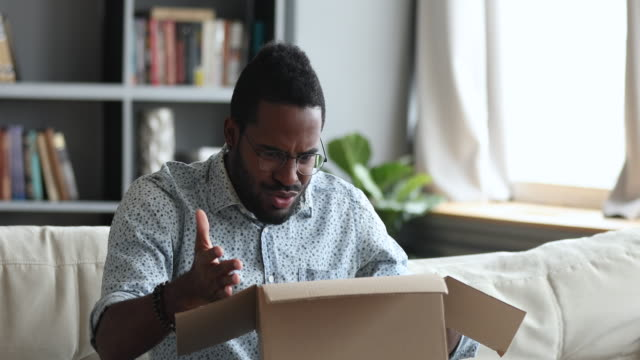 frustrated dissatisfied african man open cardboard box receive bad parcel - errore video stock e b–roll