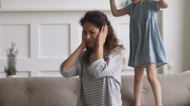 frustrated exhausted mother tired of screaming noisy kid daughter tantrum - birichinata video stock e b–roll