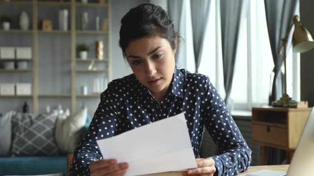 Frustrated indian girl feeling upset reading bad news in letter