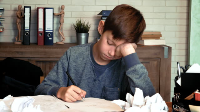 frustrated little boy tired of his homework crumples his paper - praca domowa filmów i materiałów b-roll