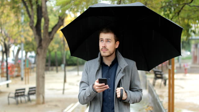 Frustrated man checking weather app on phone in a rainy day
