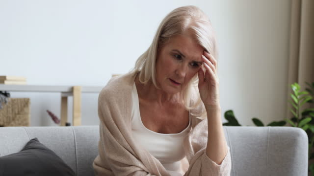 Frustrated mature old female retiree sitting on couch, feeling anxious.